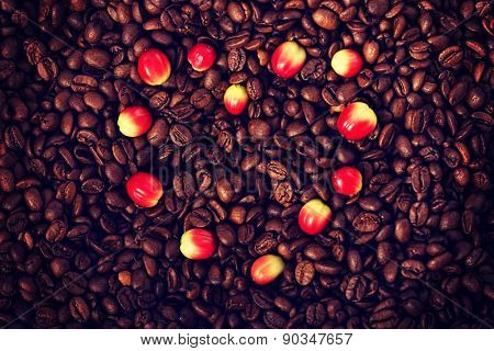 Heart shape of berries on aromatic coffee beans