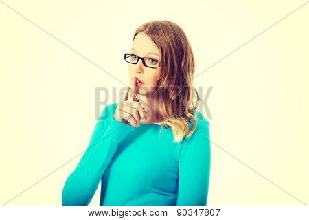 Teenage woman making silent sign with finger on lips