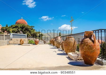 Greek church with ceramic vases on terrace, Greece