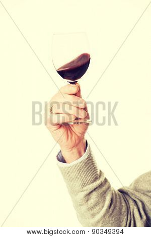 Close up on male hand holding a glass of wine.