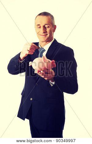 Businessman putting a coin to piggybank.
