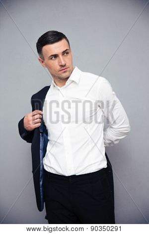 Confident businessman dressing jacket over gray background and looking away