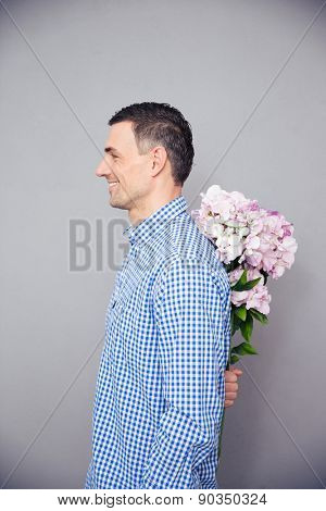 Side view portrait of a happy man hiding flower behind his back