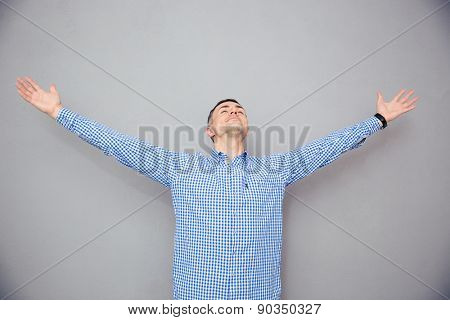 Portrait of a man gesturing freedom expression over gray background