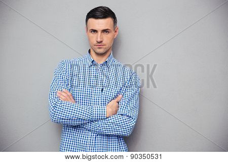 Portrait of a handsome young man with arms folded looking at camera over gray background