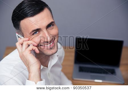 Smiling businessman talking on the phone and looking at camera