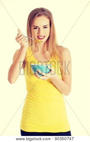 Happy blonde woman eating cereals.