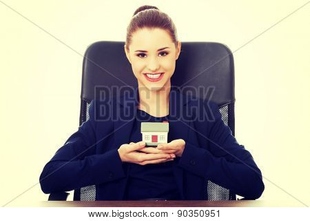 Friendly smiling businesswoman presenting a model house