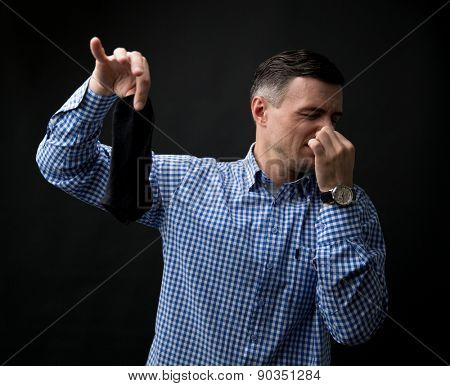 Man holding smelly socks and clogged nose over black background