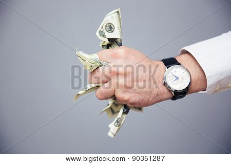 Closeup image of a businessman hand holding bills of US dollar in fist over gray background