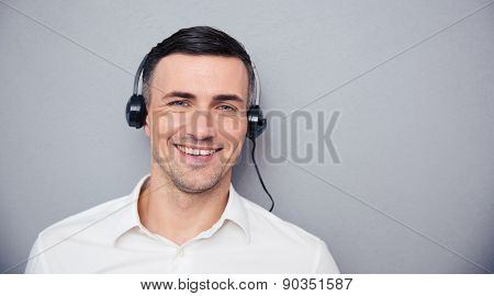 Portrait of a smiling male assistant in headphones looking at camera over gray background