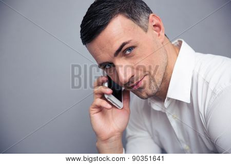 Happy businessman talking on the phone over gray background and looking at camera