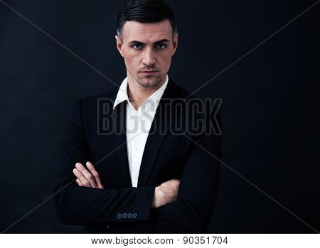 Portrait of a confident businessman with arms folded over black background. Looking at camera