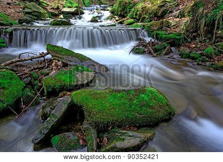Scene with green moss stones in waterfall on mountain river