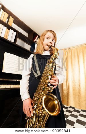 Small girl in dress plays on alto saxophone