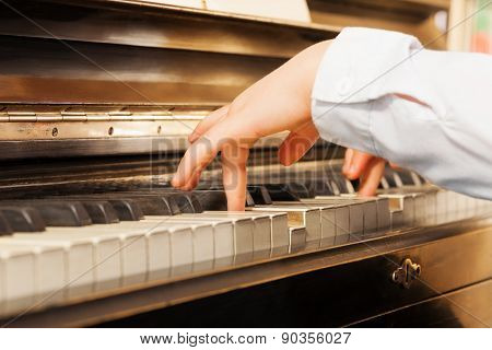Close-up view of child's hands playing on piano