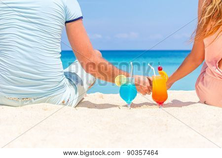 young happy couple enjoying tropical cocktails on sand beach, summer vacation