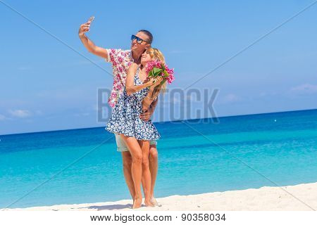 Vacation couple on beach taking pictures with camera phone. Romantic couple photographing self-portrait having fun on summer holidays travel on tropical beach