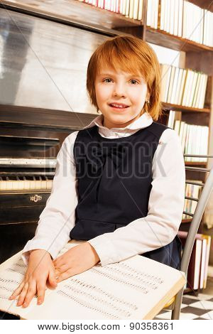 Happy girl in school uniform holding piano notes