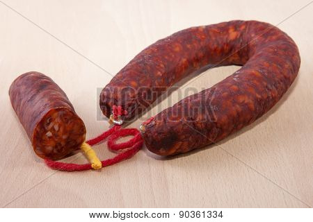 Red Iberian Chorizo With Some Cut Pieces Over Wooden Surface