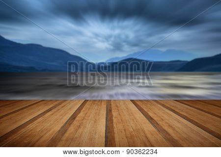 Long Exposure Landscape Of Stormy Sky And Mountains  Over Lake With Wooden Planks Floor