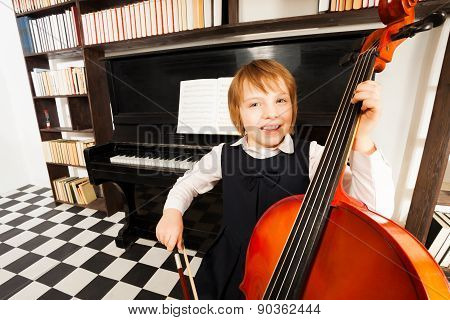 Happy kid in school dress playing on the cello
