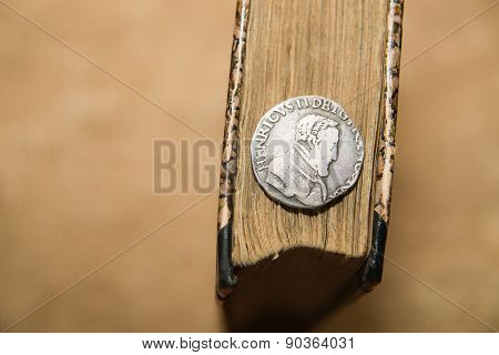 French Old Coin With A Portrait Of The King Is On The Book