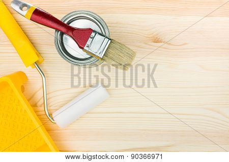 Paint Roller With Tray And Brush On Wooden Floor