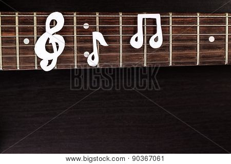 Electric guitar deck with paper treble clef on dark background