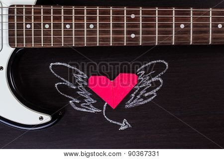 Electric guitar deck and paper heart with painted wings on dark background