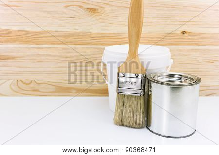 Two Cans Of Paint With Brush