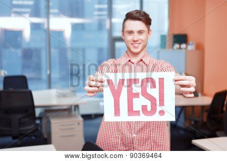 Office worker holding poster with yes slogan