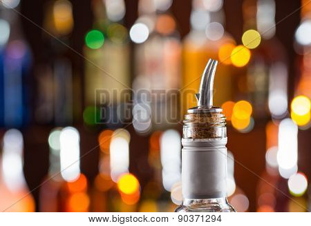 Detail of alcohol bottle with filler on bar, close-up.