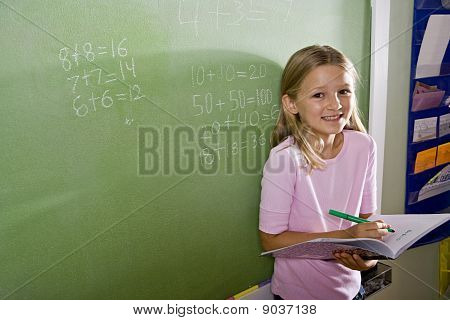 Happy Girl Doing Math On Blackboard In Class