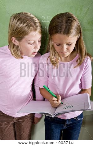 Close-up Of School Girls Writing In Class
