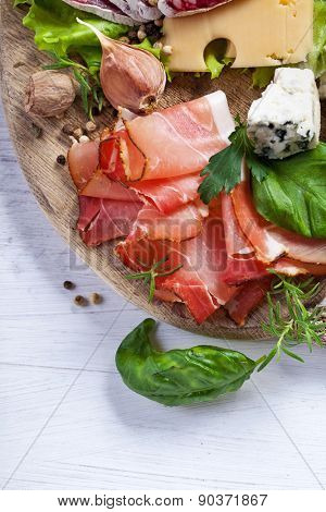 Sliced prosciutto with salami,cheese and basil on a wooden board