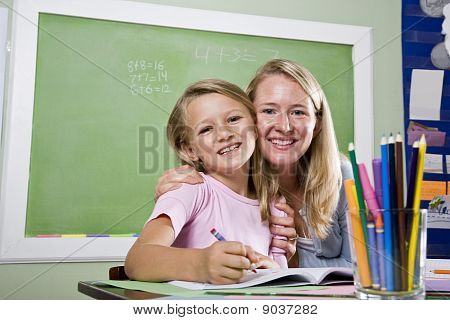 Teacher And Young Student In Class Writing