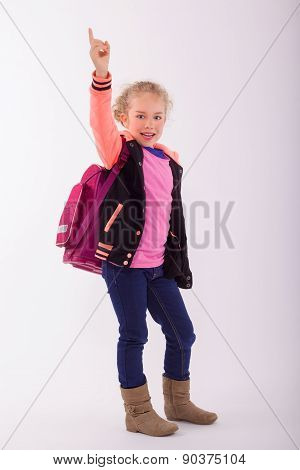 Blond small girl with school bag on the back, points with the finger in the air