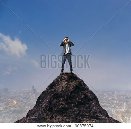 Young Business Man Standing On Top Of Mountain And Spying By Binocular Looking For Something