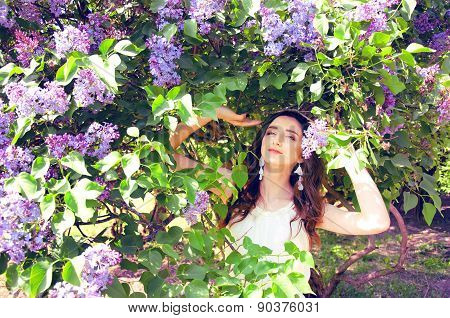 Woman With Long Brown Hair In Lilac Bushes