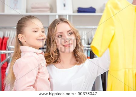 Young mother chooses dress in a store with her daughter