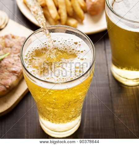Beer Being Poured Into Glass With Steak And French Fries On Wooden Background