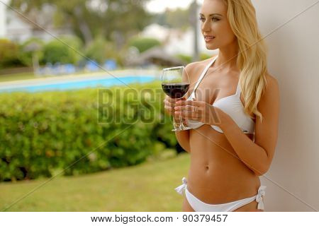 Waist Up of Blond Woman Wearing White Bikini Leaning Against Pillar and Holding Glass of Red Wine While Looking Contentedly into the Distance