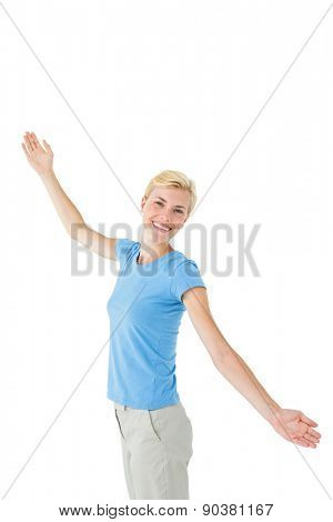 Blonde woman standing arms outstretched on white background
