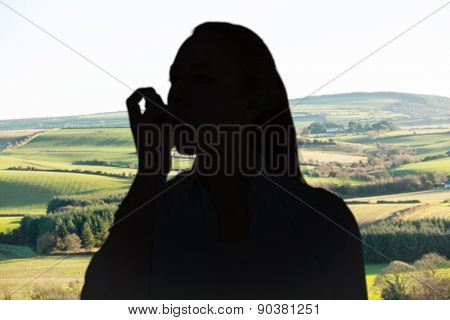 Pretty blonde using an asthma inhaler against scenic landscape