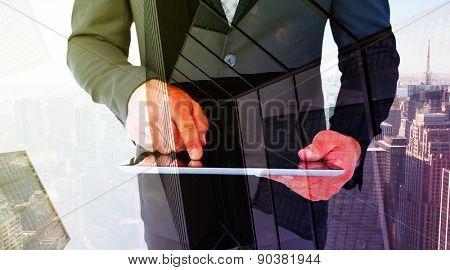 Businessman using his tablet pc against skyscraper