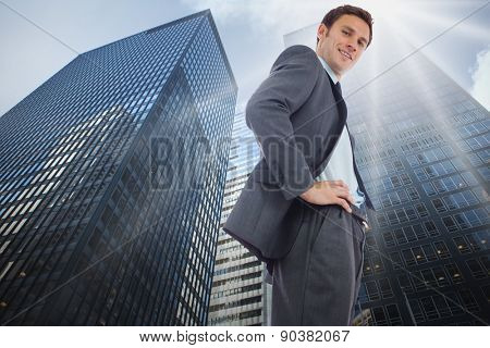 Cheerful businessman standing with hands on hips against low angle view of skyscrapers