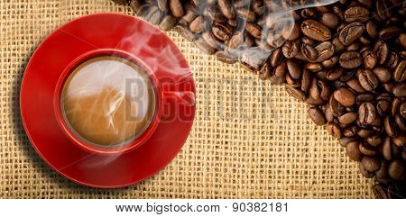 Red cup of coffee against coffee beans and burlap sack