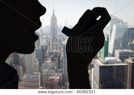 Close up of a woman using an asthma inhaler against new york