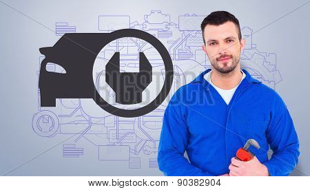 Smiling male mechanic holding monkey wrench against grey vignette